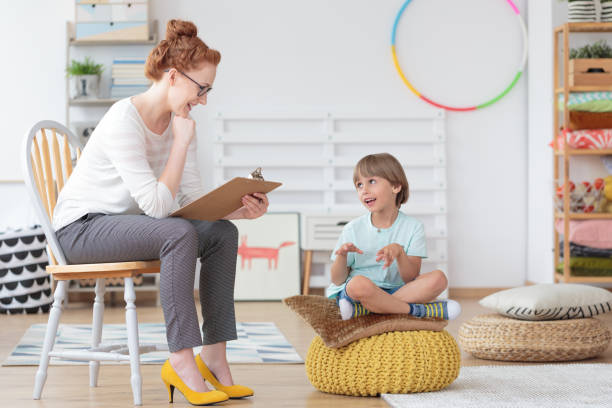 Cheerful young kid talking with helpful child counselor during psychotherapy session in children mental health center
